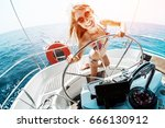 young woman in bikini steering... | Shutterstock . vector #666130912
