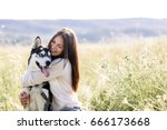 Stock photo beautiful girl plays with a dog black and white husky with blue eyes green field 666173668