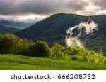 forest on grassy hillside. gorgeous cloudy sunrise in mountains - stock photo