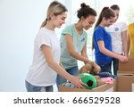 young volunteers with boxes of... | Shutterstock . vector #666529528