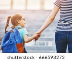 Small photo of Parent and pupil of primary school go hand in hand. Woman and girl with backpack behind the back. Beginning of lessons. First day of fall.