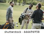 Small photo of multiethnic golf players with golf clubs having fun on golf course