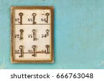 Stock photo small vintage cabinet with rusted hotel keys and room numbers on a blue eroded background 666763048