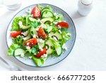 green salad with sliced avocado ...   Shutterstock . vector #666777205