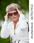 Small photo of Portrait of senior European woman with temporal headache, outdoor