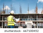 Engineering Consulting People on construction site holding blueprint in his hand. Building  inspector. Construction site check drawing and business workflow of new building - stock photo