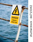 electric shock danger sign on fencing over water - stock photo