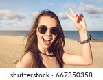 Small photo of Happy young girl in sunglasses showing peace gesture and looking at camera while standing on a seashore