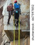Small photo of Two climbers work on the route entrenched on a rocky ledge. Climbing gear and equipment closeup.