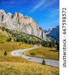 """Small photo of """"Indian summer"""" in the Tyrol. Picturesque road through the Sella Pass, Dolomites. The concept of extreme and ecological tourism. Impressive ridge of dolomite rocks"""