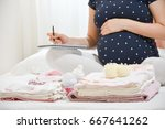pregnant woman is packing baby... | Shutterstock . vector #667641262