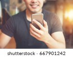 happy man using smartphone at... | Shutterstock . vector #667901242