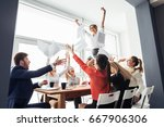 Small photo of picture of happy business team celebrating victory in office. woman stand on table