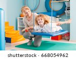 woman helping a smiling boy to... | Shutterstock . vector #668054962
