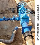 Small photo of Oil, gas, water industry. Wellhead with valve armature underground. Dug deep trench utilities engineering urban systems.