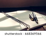 pen and book on wood background ...   Shutterstock . vector #668369566