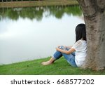 Small photo of The girl leaning on a tree near the river eye look forward aimlessly/hope/Beautiful woman wearing white clothes sit on the river bank to use the image background