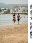 Small photo of Alanya, Turkey - May, 11, 2017: A man and a woman of African nationality walk along the beach along the coastline. Girl in a bikini, he is dressed in a black bathing suit.