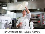 chef tossing pizza dough  | Shutterstock . vector #668873998