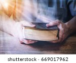 man hands holding holy bible on ... | Shutterstock . vector #669017962