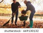 Mature Couple Raking Autumn...