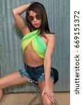 Small photo of Pretty petite brunette in a green scarf and cutoff jeans