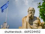 Small photo of Close-up statue of the philosopher Socrates on the background of the Greek Flag.