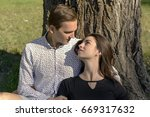 beautiful young couple sitting...   Shutterstock . vector #669317632