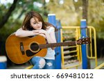 Small photo of Beautiful Asian girl sitting hugging guitar on playground Cozy atmosphere vintage. During the summer holidays Playing a musical instrument is a good mental condition.