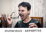 Small photo of a man with funny accident, he accidentally jab his eye with glasses leg and get painful reaction