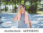 Small photo of Young runner, eat apple and rest after exercise.Film look photo