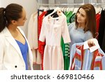 Small photo of Cheerful shop assistant helping her female customer choosing dresses working at the store profession occupation friendly helpful advise people lifestyle consumerism purchasing positivity retail sales