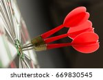 Stock photo three red darts pinned right on the center of target 669830545