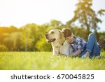 Stock photo young boy and his dog lying on the grass together happy boy hugging his pet labrador smiling with 670045825