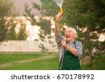 senior gardener with water hose.... | Shutterstock . vector #670178992