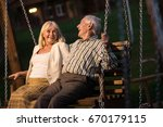 couple on porch swing  evening. ... | Shutterstock . vector #670179115