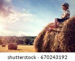 Boy Sitting On A Haystack In...
