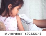 doctor injecting vaccination in ... | Shutterstock . vector #670323148