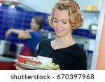 young blonde waitress holding... | Shutterstock . vector #670397968