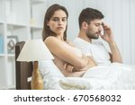 the sad couple sit on the bed | Shutterstock . vector #670568032