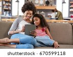 mother and daughter sit on sofa ... | Shutterstock . vector #670599118