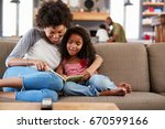 mother and daughter sit on sofa ... | Shutterstock . vector #670599166