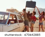 Stock photo friends loading luggage onto car roof rack ready for road trip 670642885