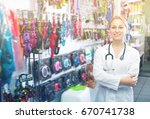 Stock photo young woman vet recommending on goods for pets in pet shop 670741738