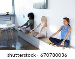 executives doing yoga in office | Shutterstock . vector #670780036
