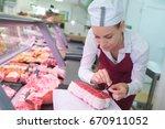female butcher tying joint of... | Shutterstock . vector #670911052