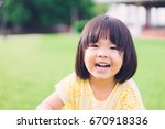 little asian girl smiling with... | Shutterstock . vector #670918336