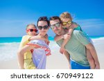 young family of four on beach... | Shutterstock . vector #670949122
