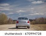 Stock photo silver car on a gravel road against a blue sky with clouds back view car journey 670994728
