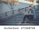 young bearded businessman sits... | Shutterstock . vector #671068768